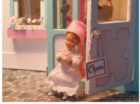 Doll emerges from the dollhouse bakery with a cupcake.